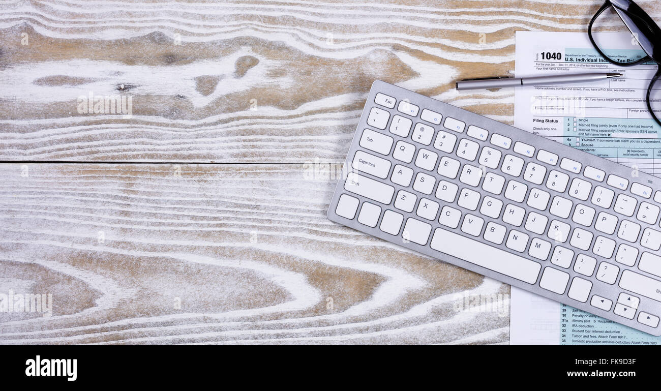 Overhead view of tax form, pen, keyboard, and reading glasses on fading white desktop. - Stock Image