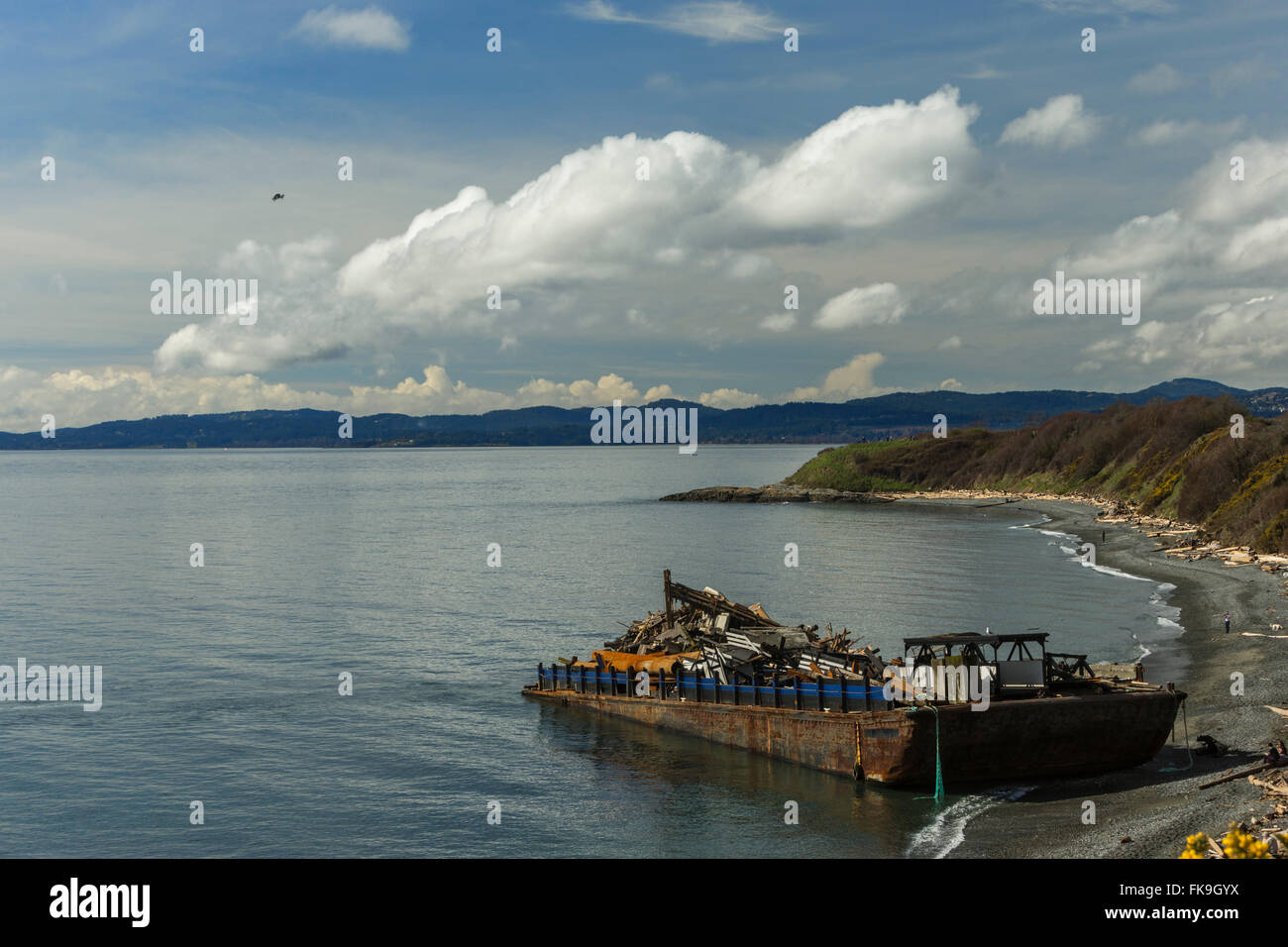 Beached barge with load of junk at Clover Point beach-Victoria, British Columbia, Canada. - Stock Image