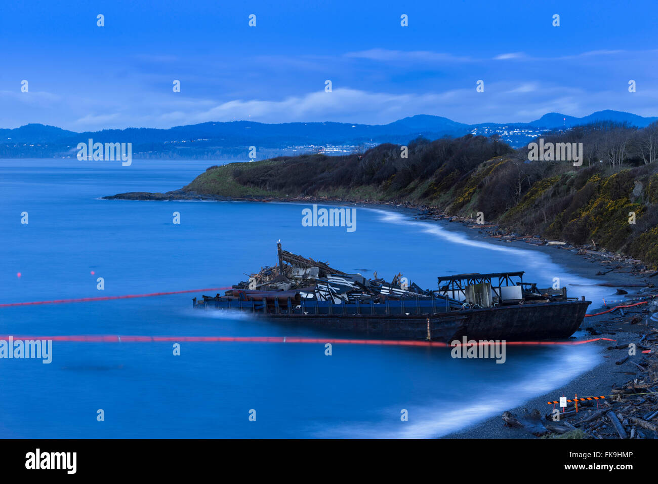 Stranded beached barge loaded with construction debris on Clover Point beach-Victoria, British Columbia, Canada. - Stock Image