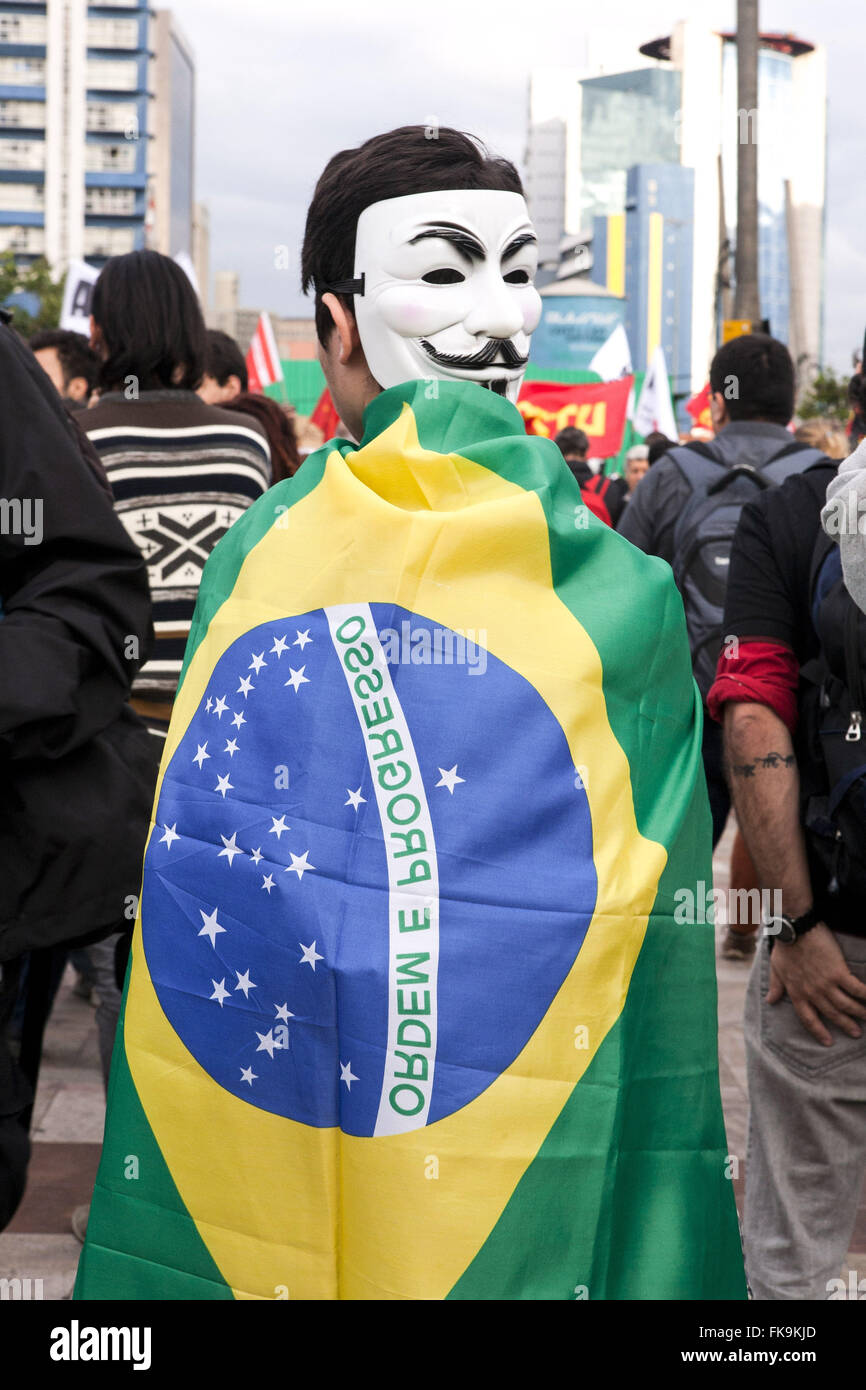 Manifestation with anonymous masks and flag of Brazil during the outbreak - Stock Image