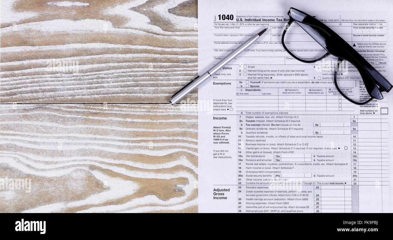 Overhead view of tax form, pen, and reading glasses on fading white desktop. - Stock Image