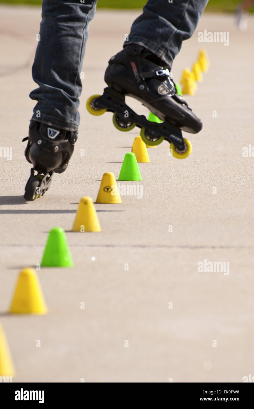Skater dodging obstacles on the ground in park - Stock Image