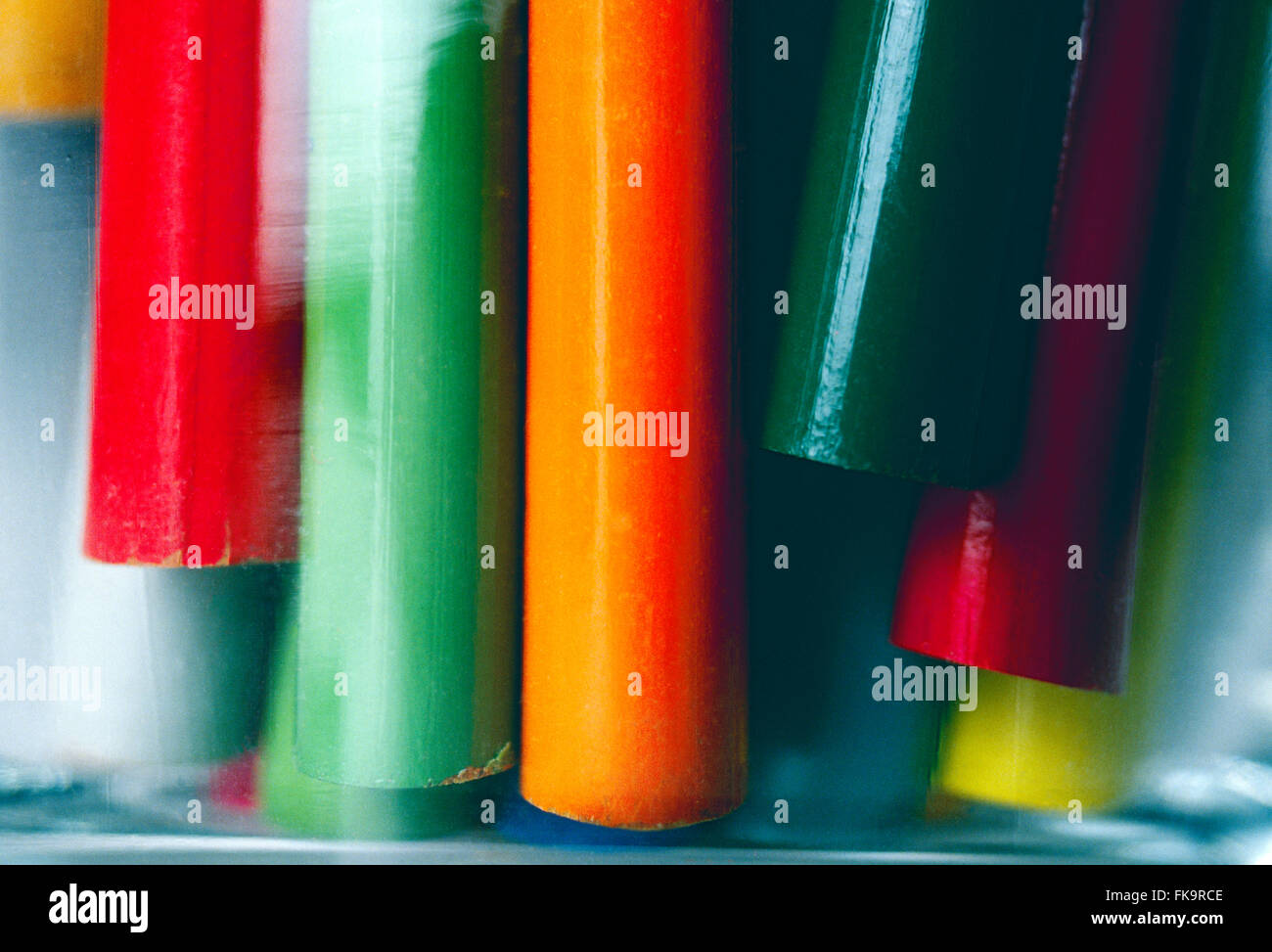 Close-up of colorful drawing pencils in a glass jar - Stock Image
