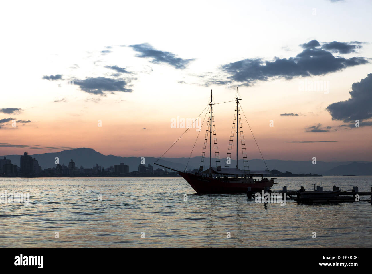 View of the sunset with schooner anchored on the beach - Stock Image