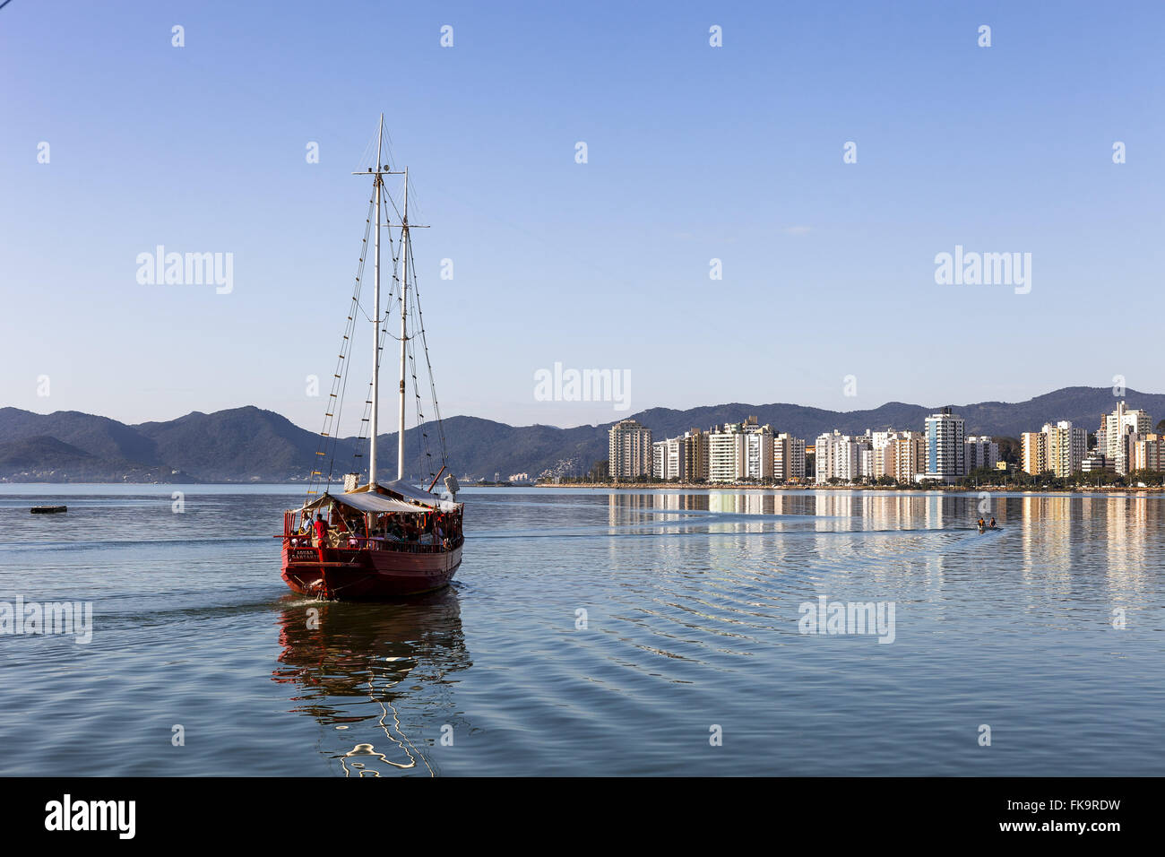 Schooner anchored in the sea with city to the bottom - Stock Image