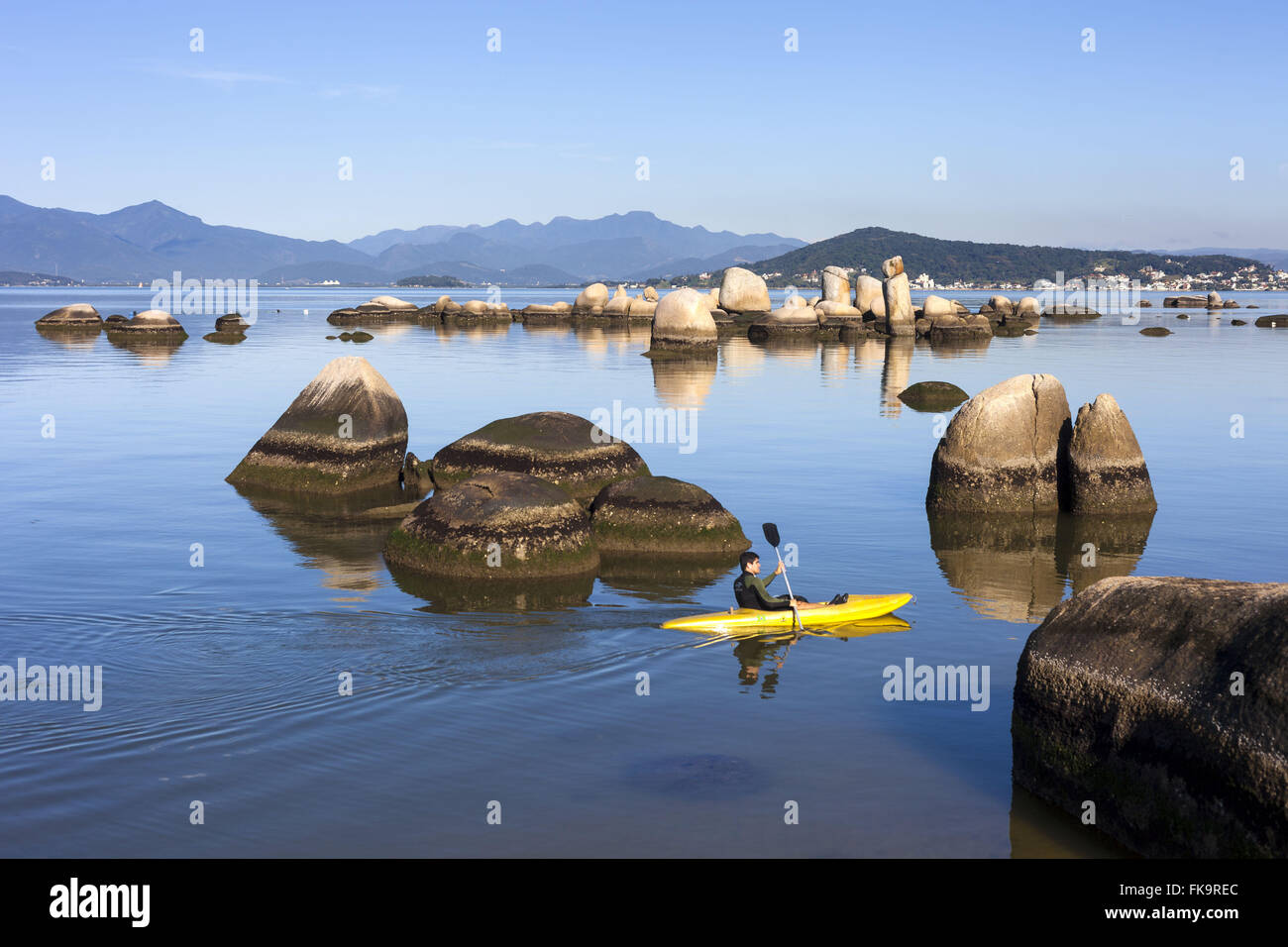 Kayaking between the rounded rock formations of Itaguacu Beach - Stock Image