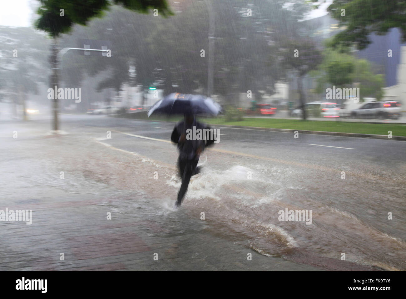 Man jumps resulting stream runoff at Avenida Sumare - Stock Image