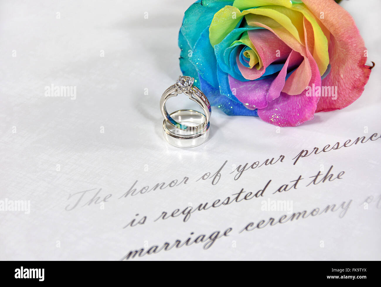 Wedding rings and rainbow rose on traditional wedding invitation ...