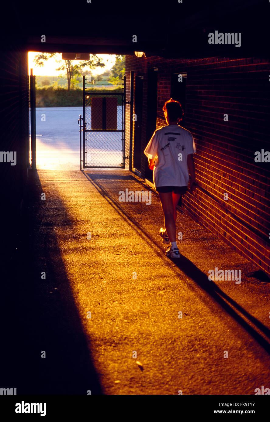 Sunset illuminates female runner leaving stadium track through tunnel - Stock Image