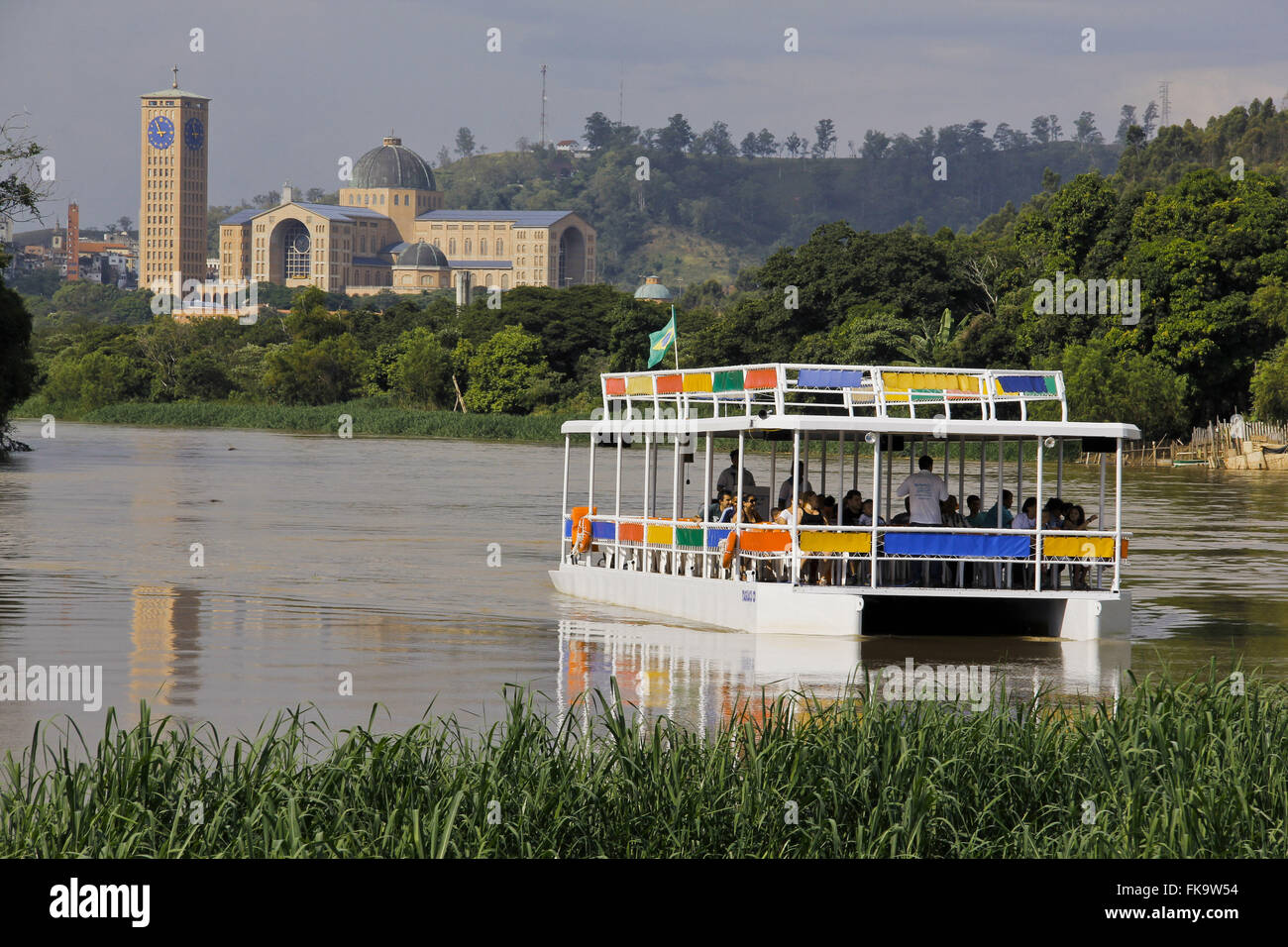 Tourists on ferry ride on the Rio Paraiba do Sul with New Basilica in the background - Stock Image