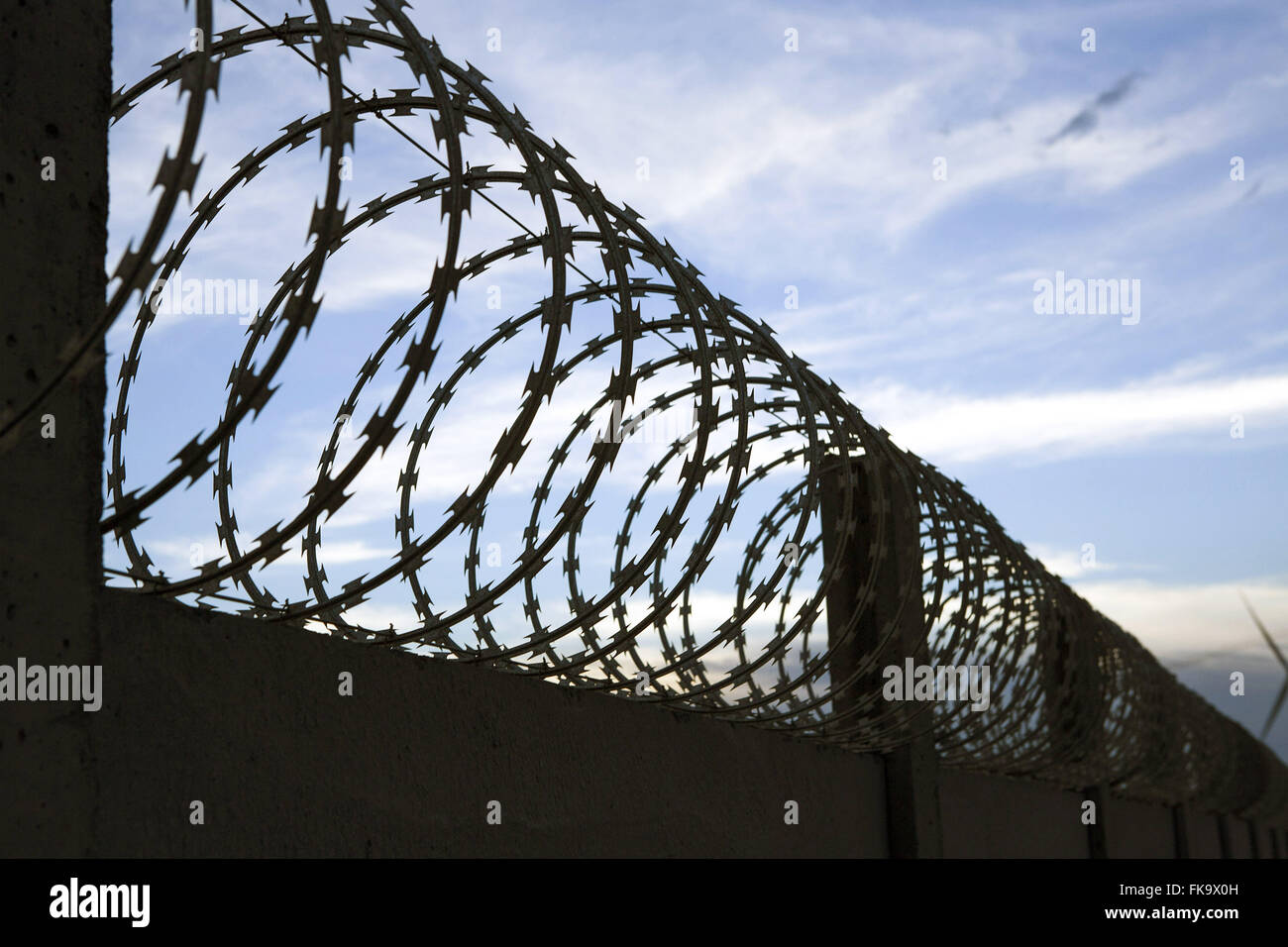 Fence with barbed wire in a secure area of the wind farm Source of the Winds - Stock Image