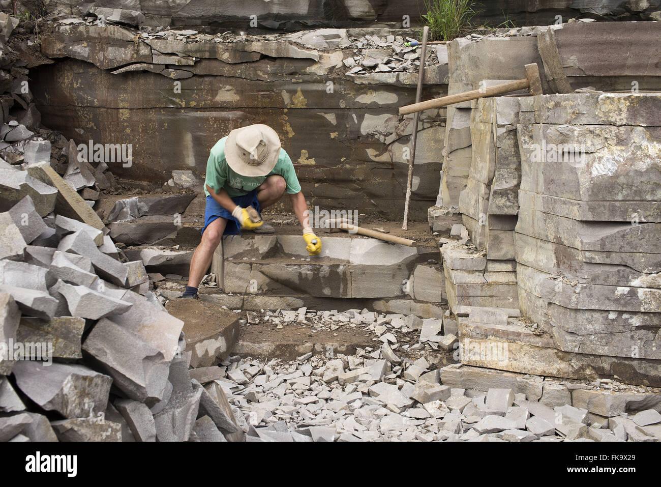 Worker extracting basaltic rocks - Stock Image