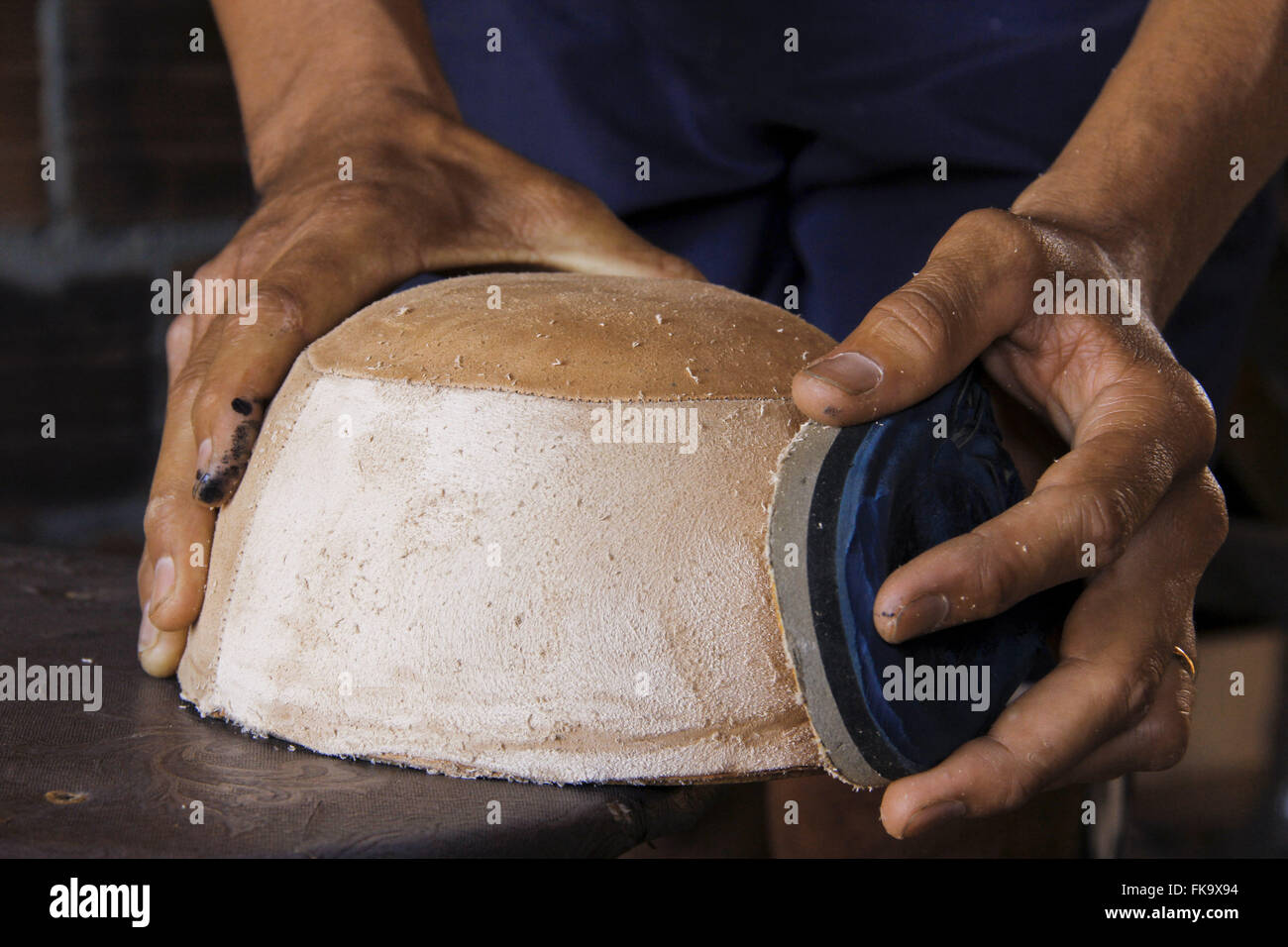 Autonomous worker sanding mold manufactures handmade hats in the village of Alegre - Stock Image