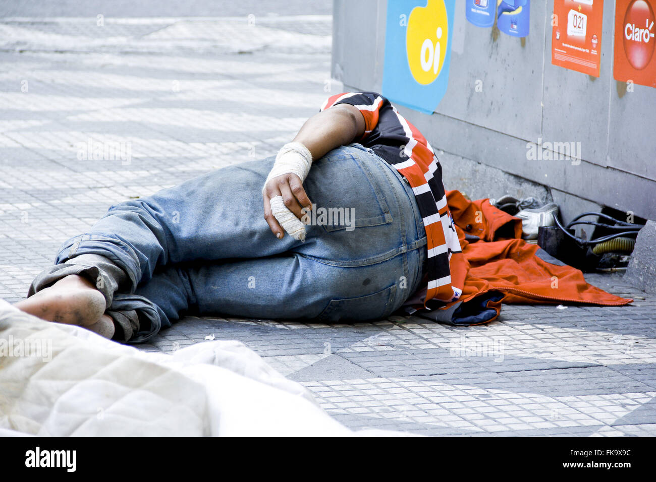Homeless man with the bandaged wrist and finger sleeping on sidewalk - Stock Image