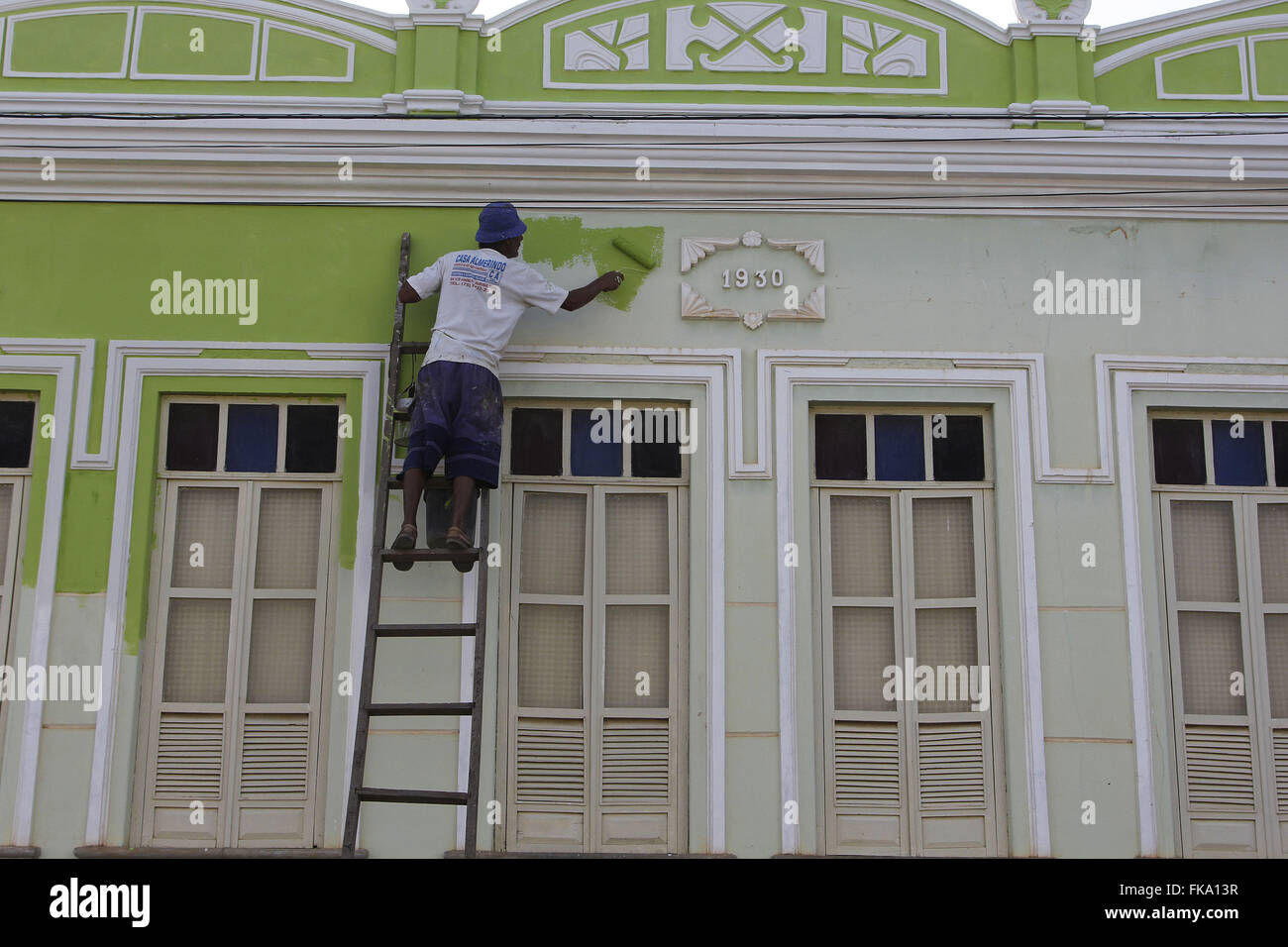 Worker painting facade of colonial townhouse - Stock Image