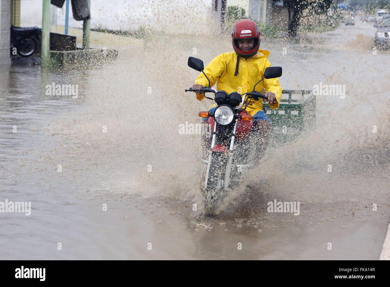 Biker traveling at street runoff during storm - Stock Image