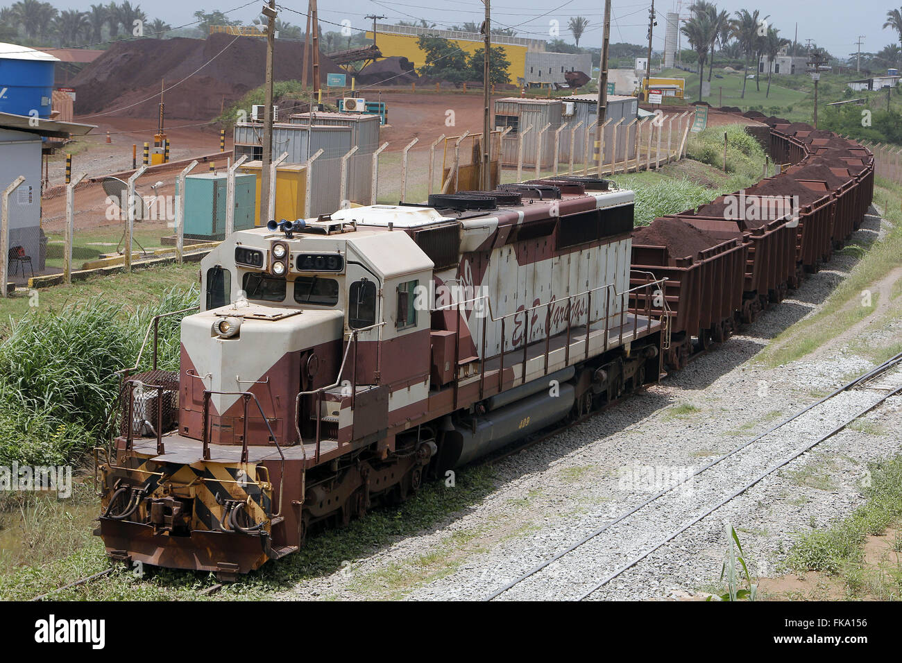 Freight train carrying iron ore on the railroad - Stock Image