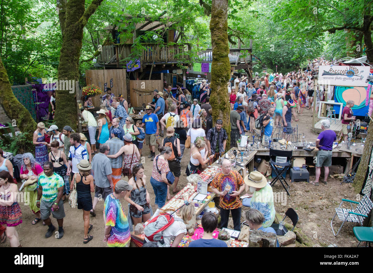 Visitors wander through one of many wooded lanes an the Oregon Country Fair - Stock Image