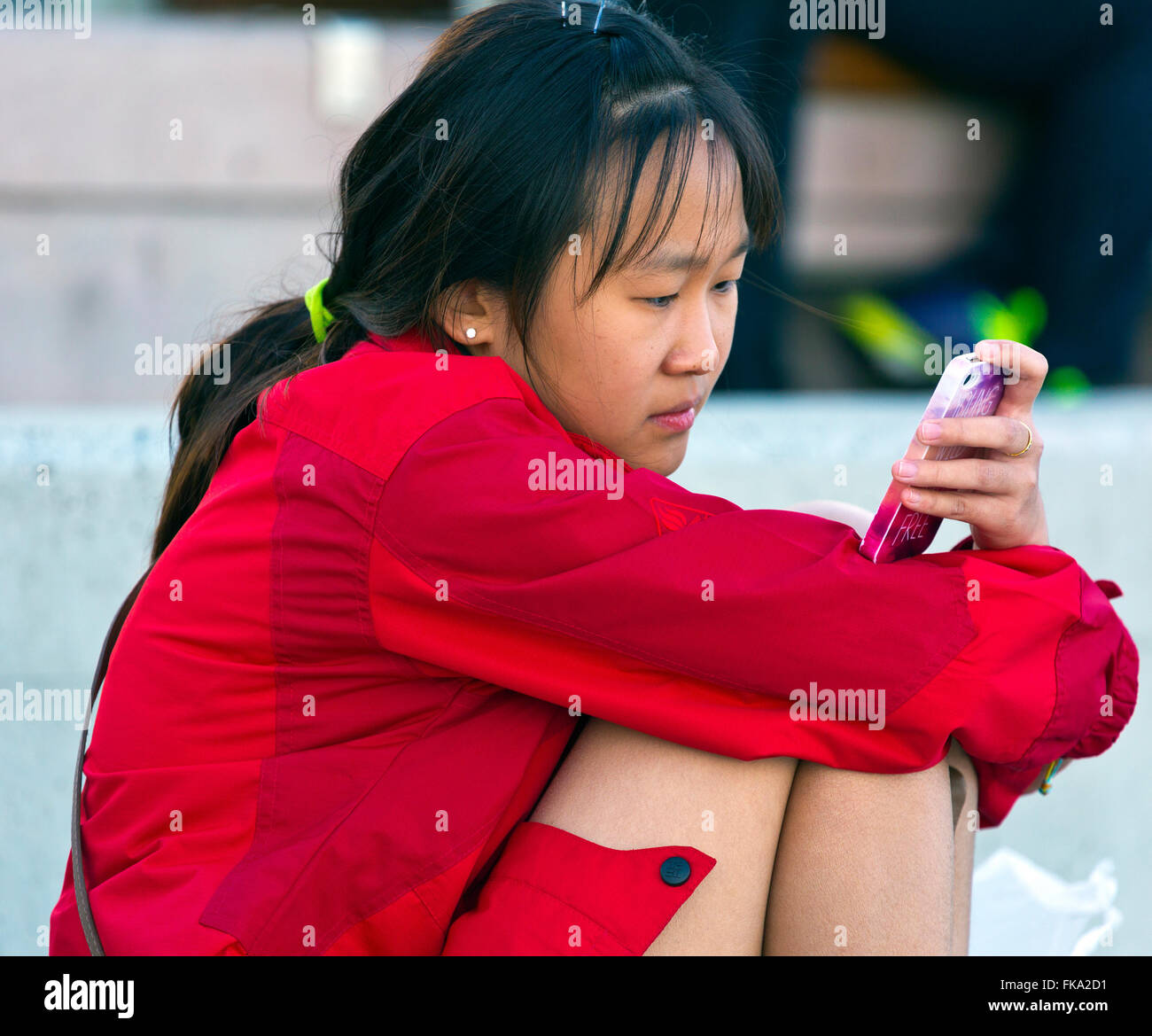 Young pretty Chinese Girl with long black hair, wearing red coat using mobile phone whilst sitting. Gold Coast, - Stock Image