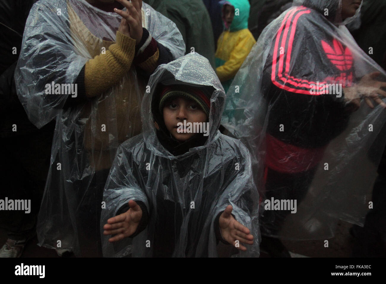 Athens, Greece. 7th Mar, 2016. Refugees and migrants stand in the rain at the Greece-FYROM buffer zone, awaiting - Stock Image