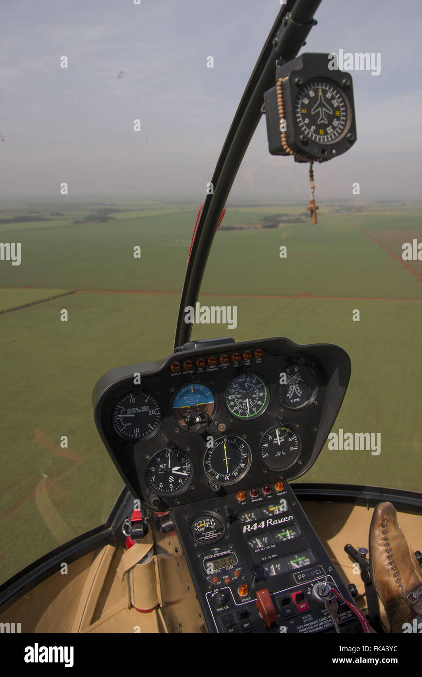 Cabin Robinson 44 helicopter flying plantation of cane sugar - Stock Image