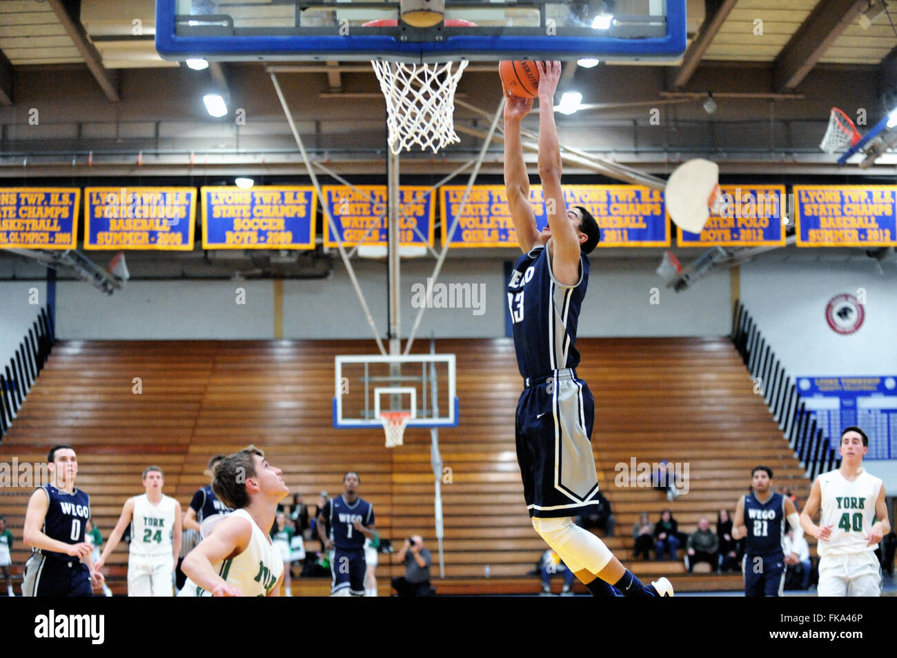 A high school player goes for a slam dunk while defensively unchallenged during a post season playoff game. USA. - Stock Image