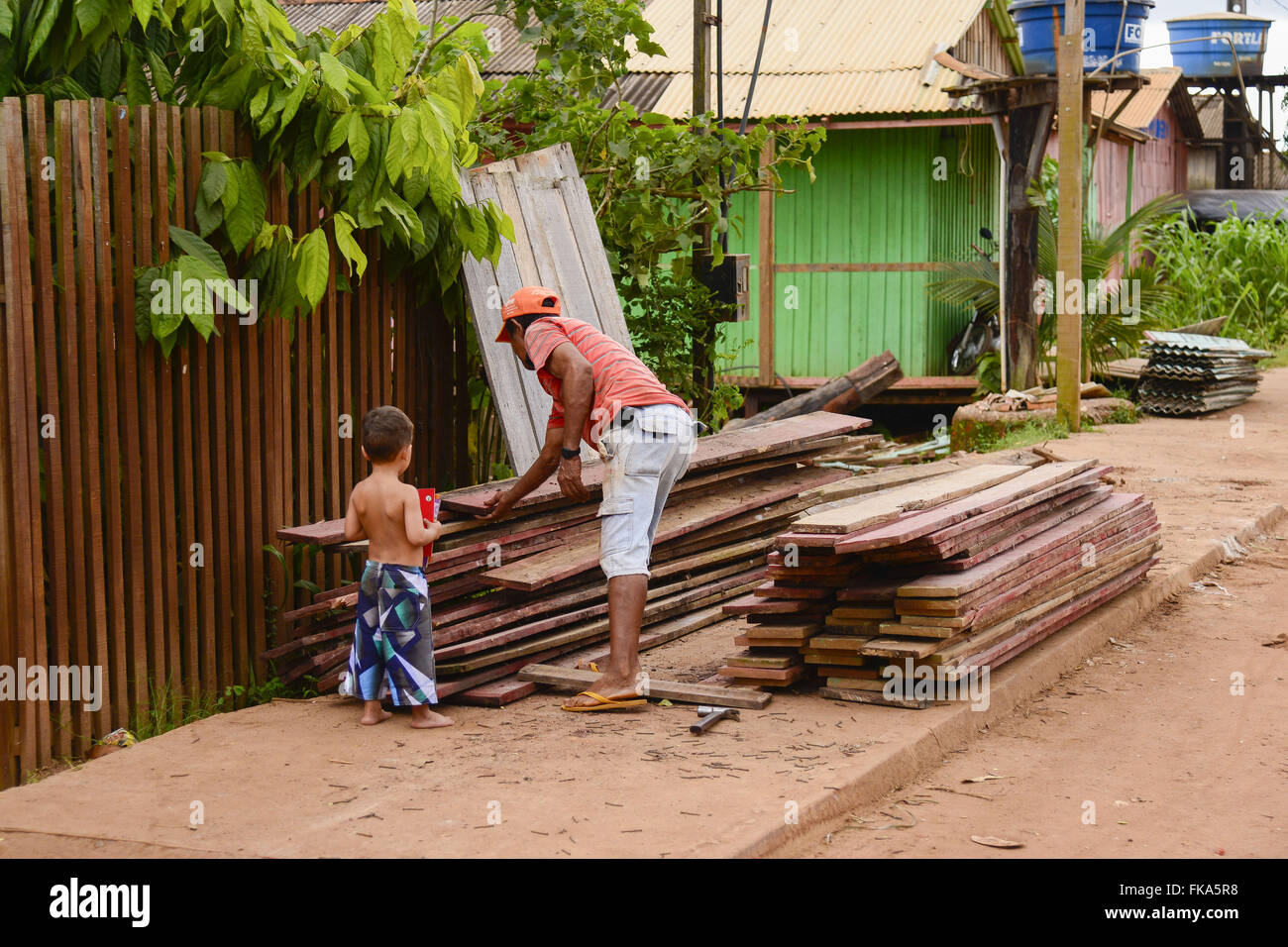 Father and son joining wooden stilts removal of the creek Ambe - Stock Image