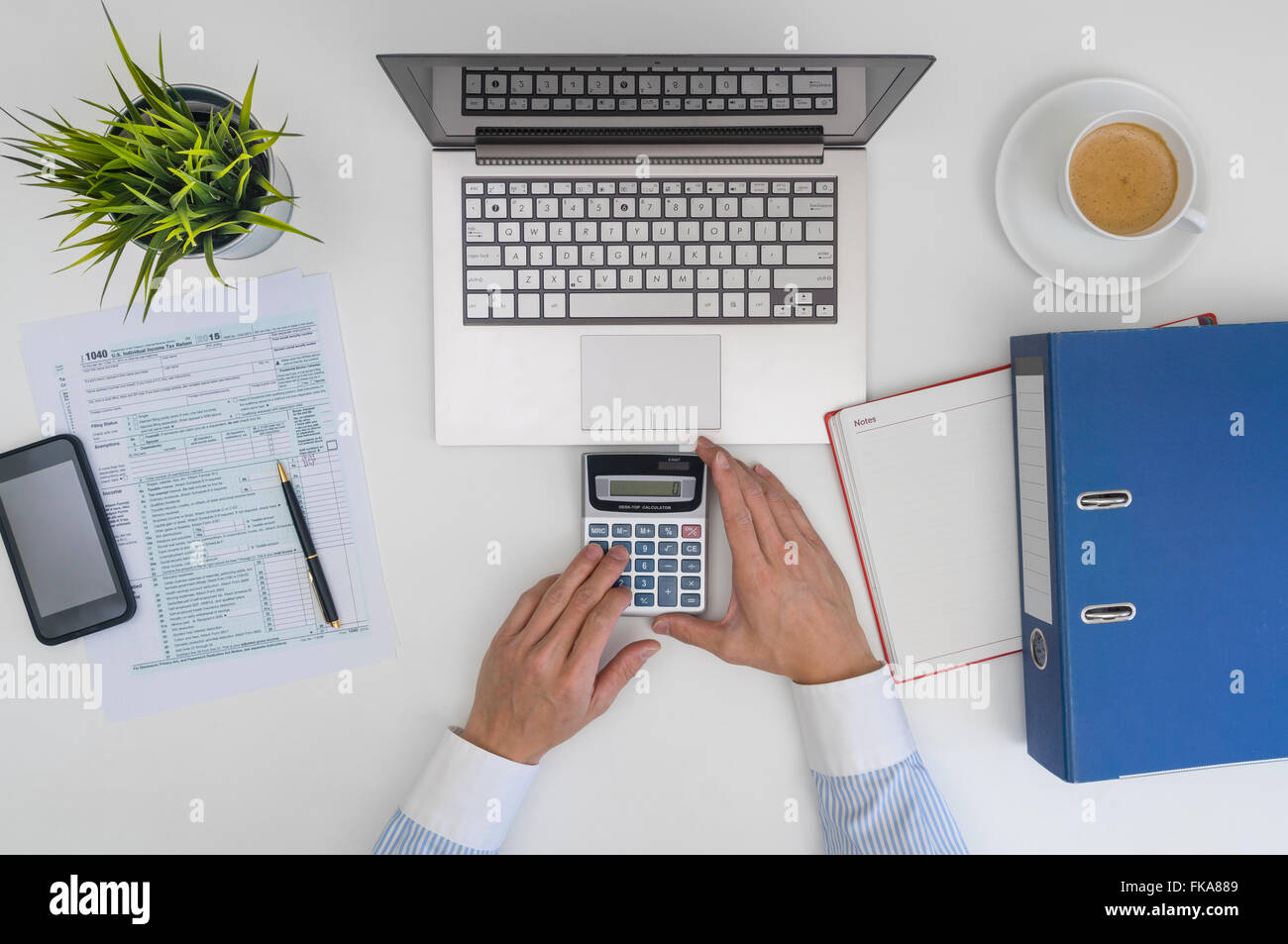 Businessman making calculation and filling tax form - Stock Image