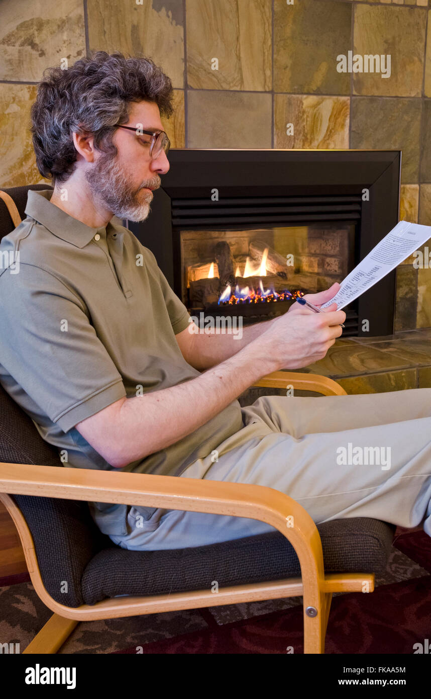 Distinguished middle-aged Caucasian male sitting near a fireplace reading an academic or financial report. - Stock Image