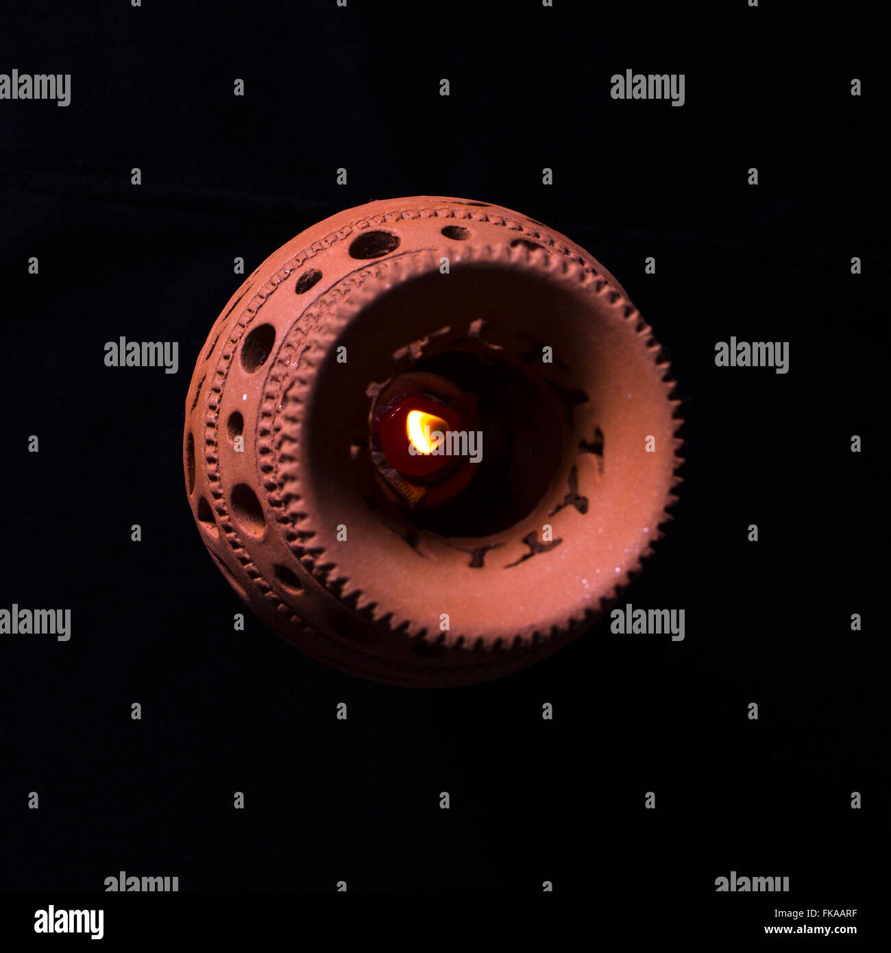 craft lamp with a lit candle inside on black background Stock Photo