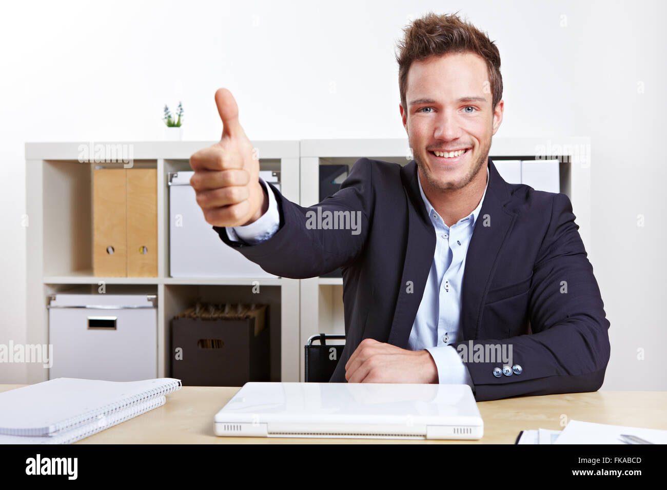 successful business man in office holding his thumbs up stock photo