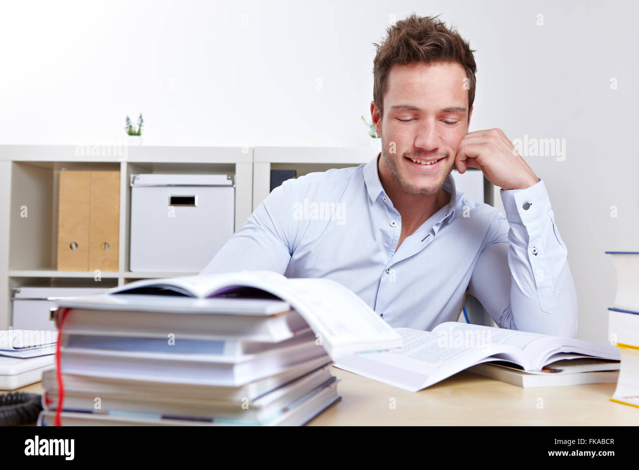 Happy college student learning with books at desk for exams Stock Photo