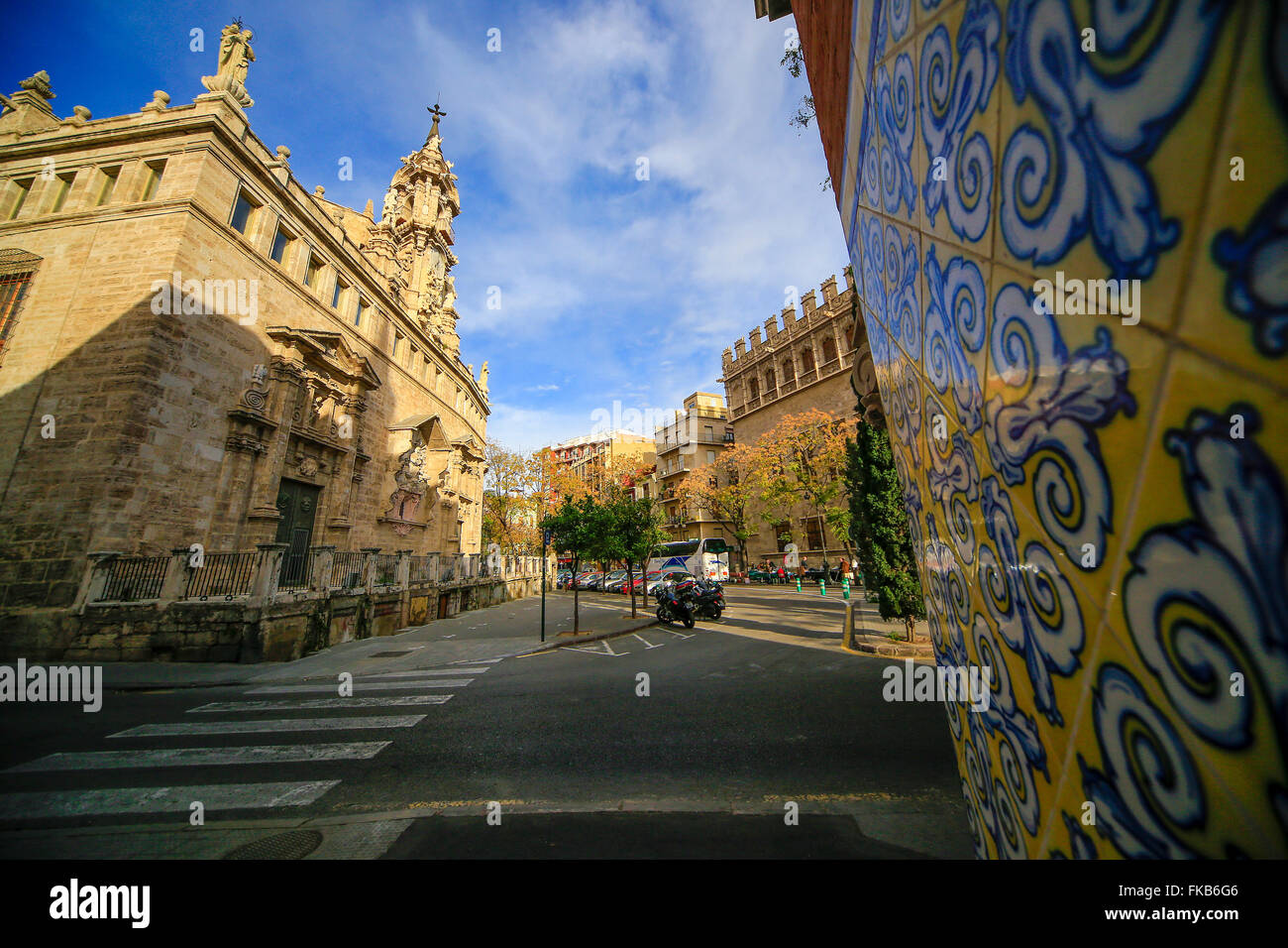 Spanish wall tiles yellow white and blue with church and pedestrian crossing - Stock Image