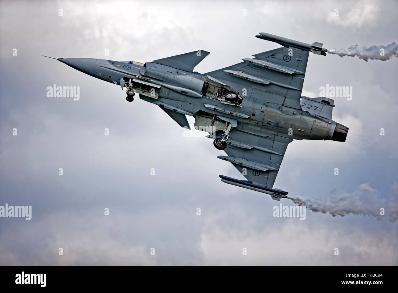 A Saab JAS 39C Gripen F 7, Swedish Air Force, Satenas, 39227, '227', takes off into an overcast sky at an - Stock Image