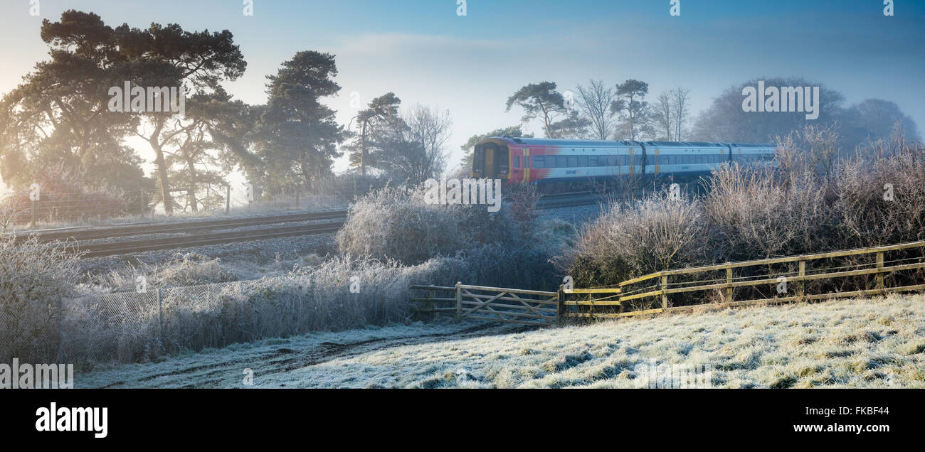 the train from Exeter to London Waterloo passing on a frosty morning at Milborne Wick, Somerset, England - Stock Image