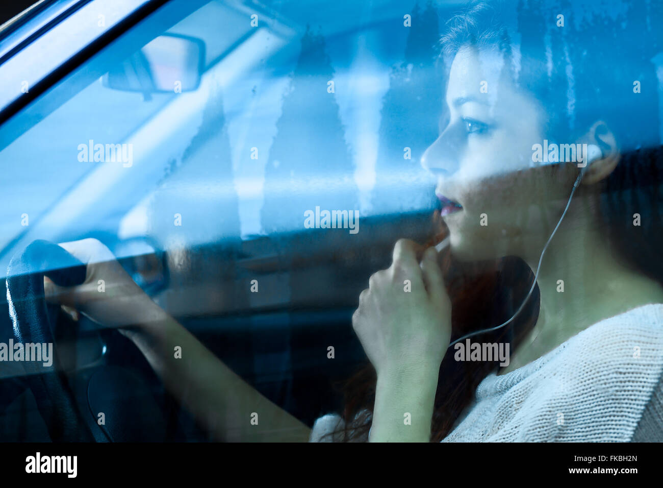 Woman Speaking in a Microphone with Earbuds while Driving a Car - Stock Image