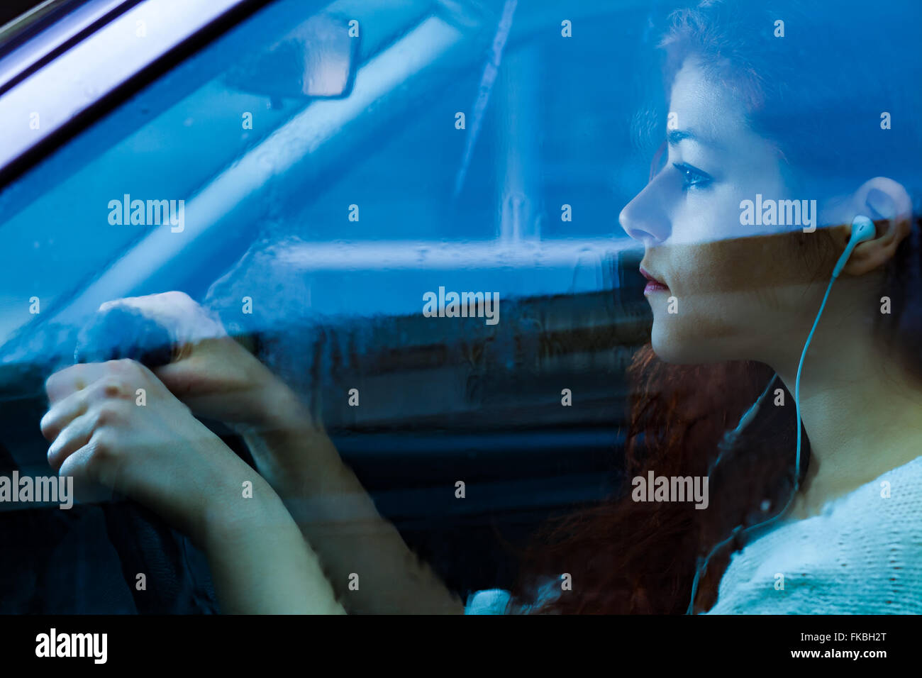 Woman with Earbuds Driving a Car on a Rainy Day - Stock Image