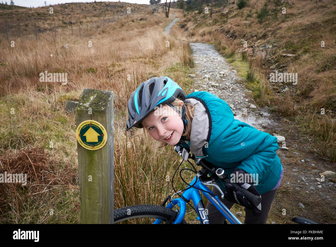 A girl smiles and laughs riding her bike offroad on a track - Stock Image