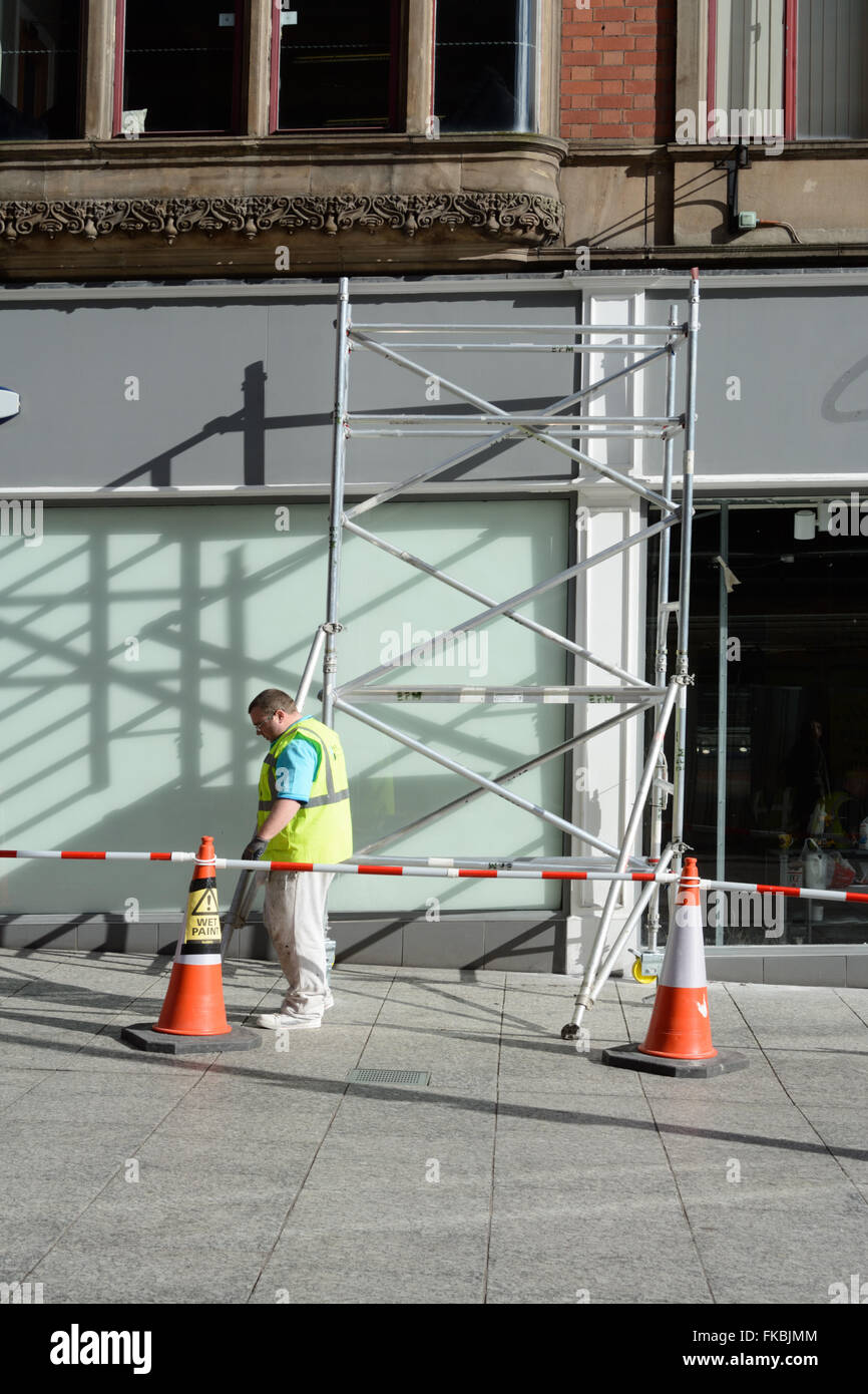 Scaffolding for painting outside a shop. - Stock Image