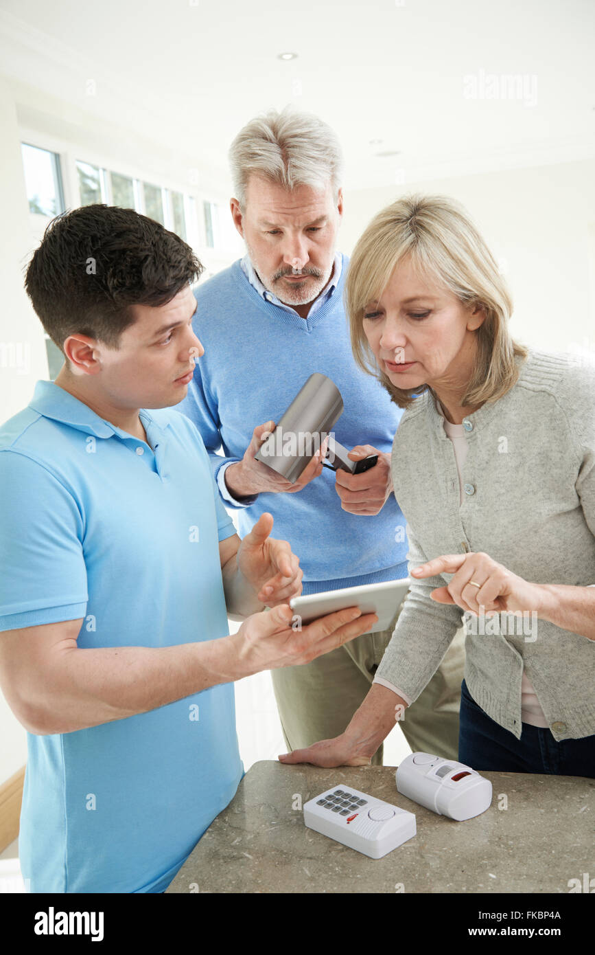 Security Consultant Demonstrating Alarm System To Mature Couple - Stock Image