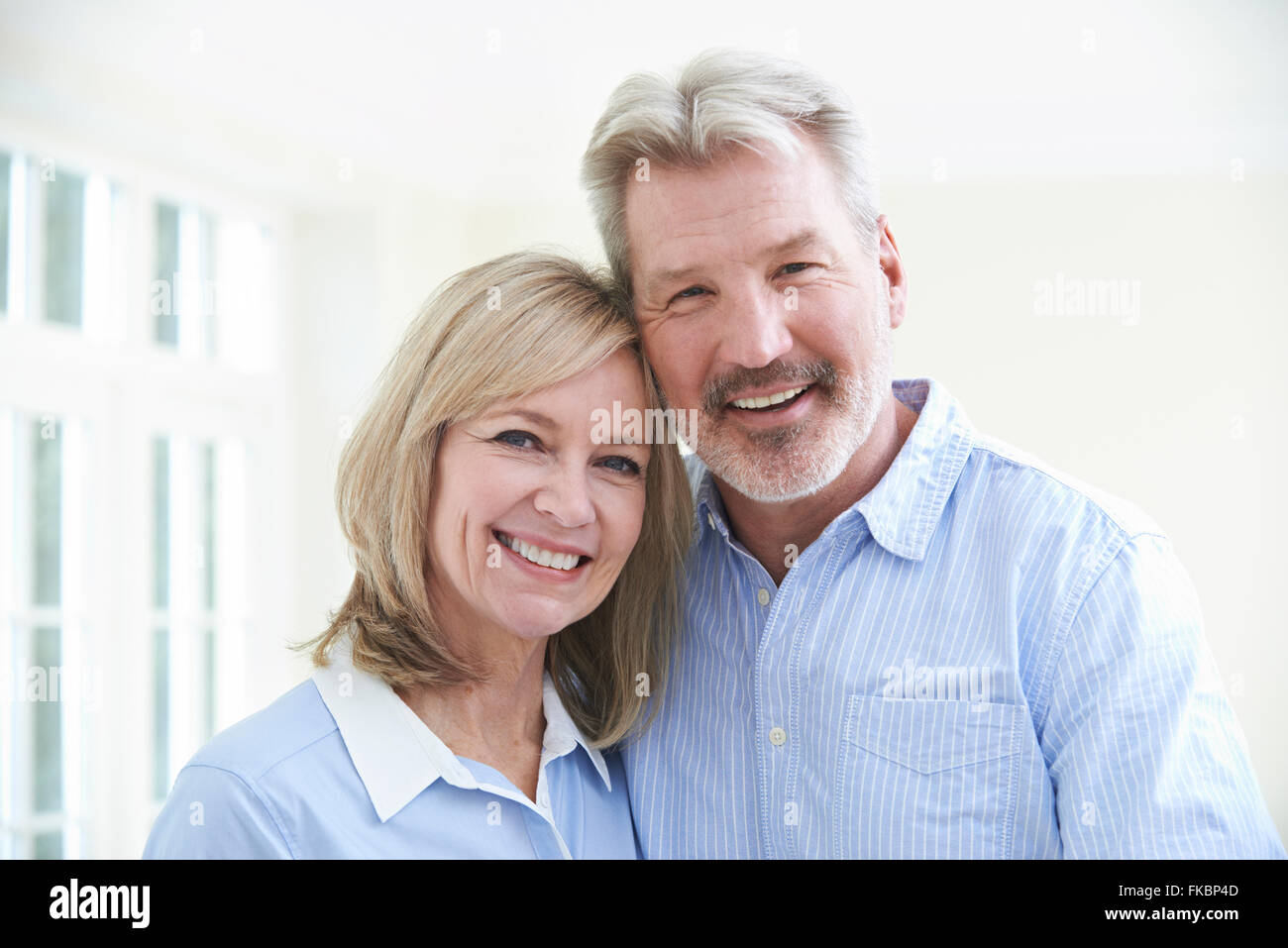 Portrait Of Loving Mature Couple At Home - Stock Image