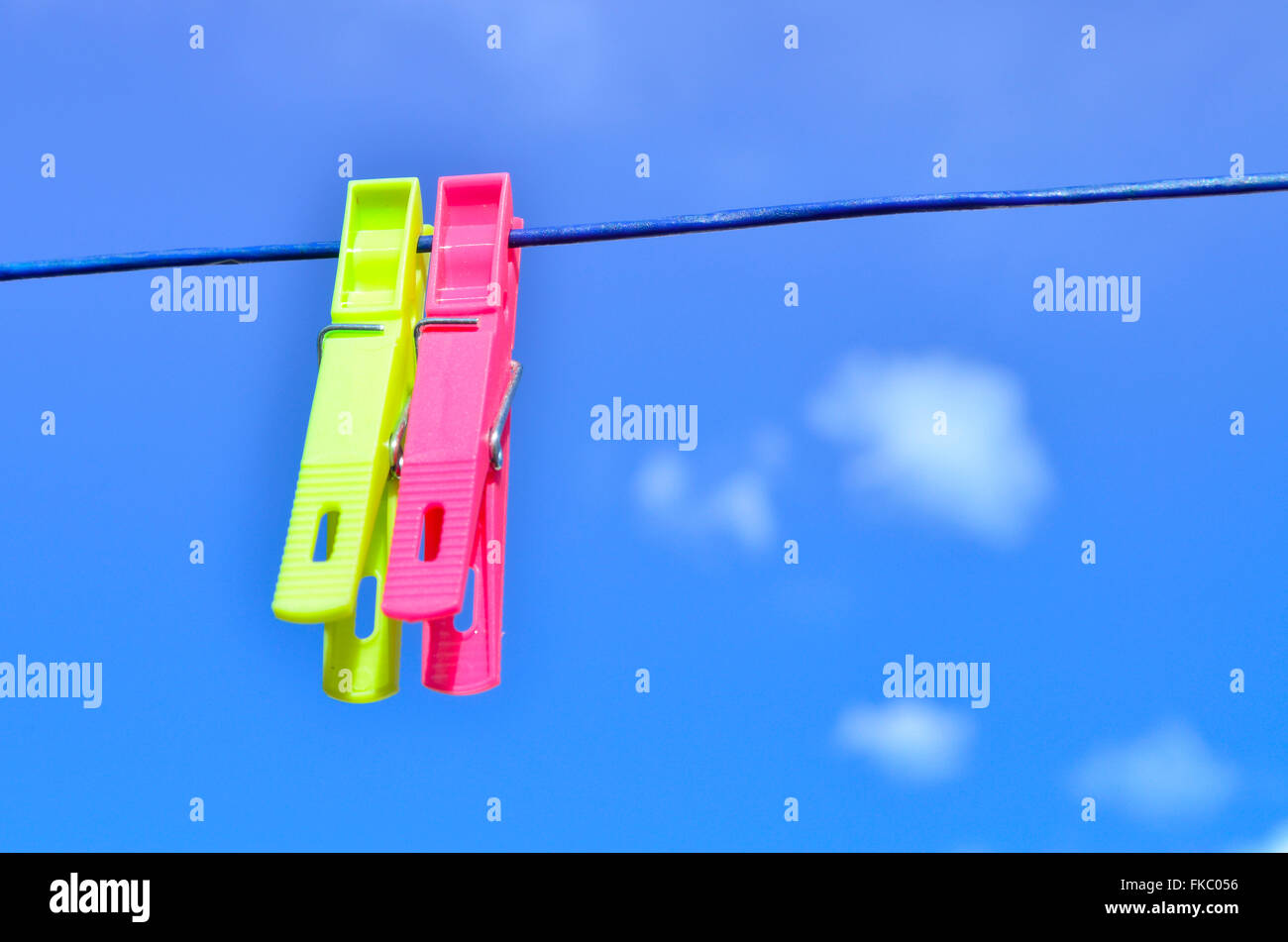 Plastic clothes pegs on washing line. - Stock Image