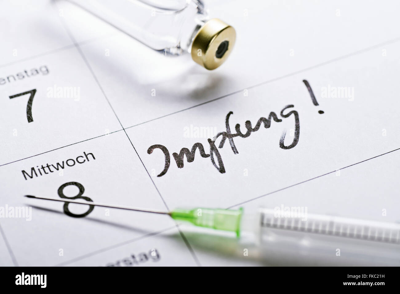 """appointment book with the word """"Impfung"""" for vaccination, a syringe and a vial of vaccine. Stock Photo"""