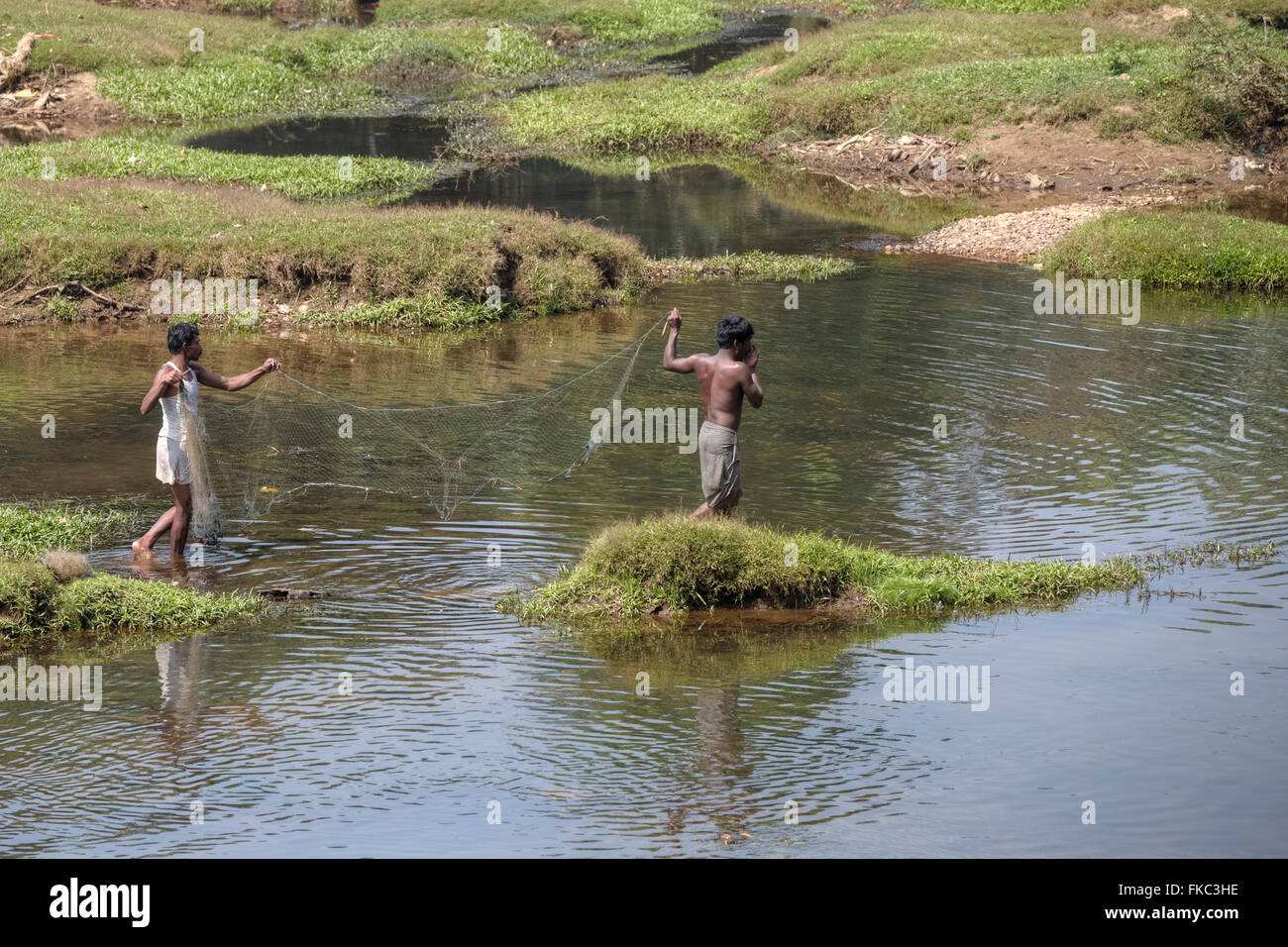 men fishing with a net in a river in Kerala, South India - Stock Image