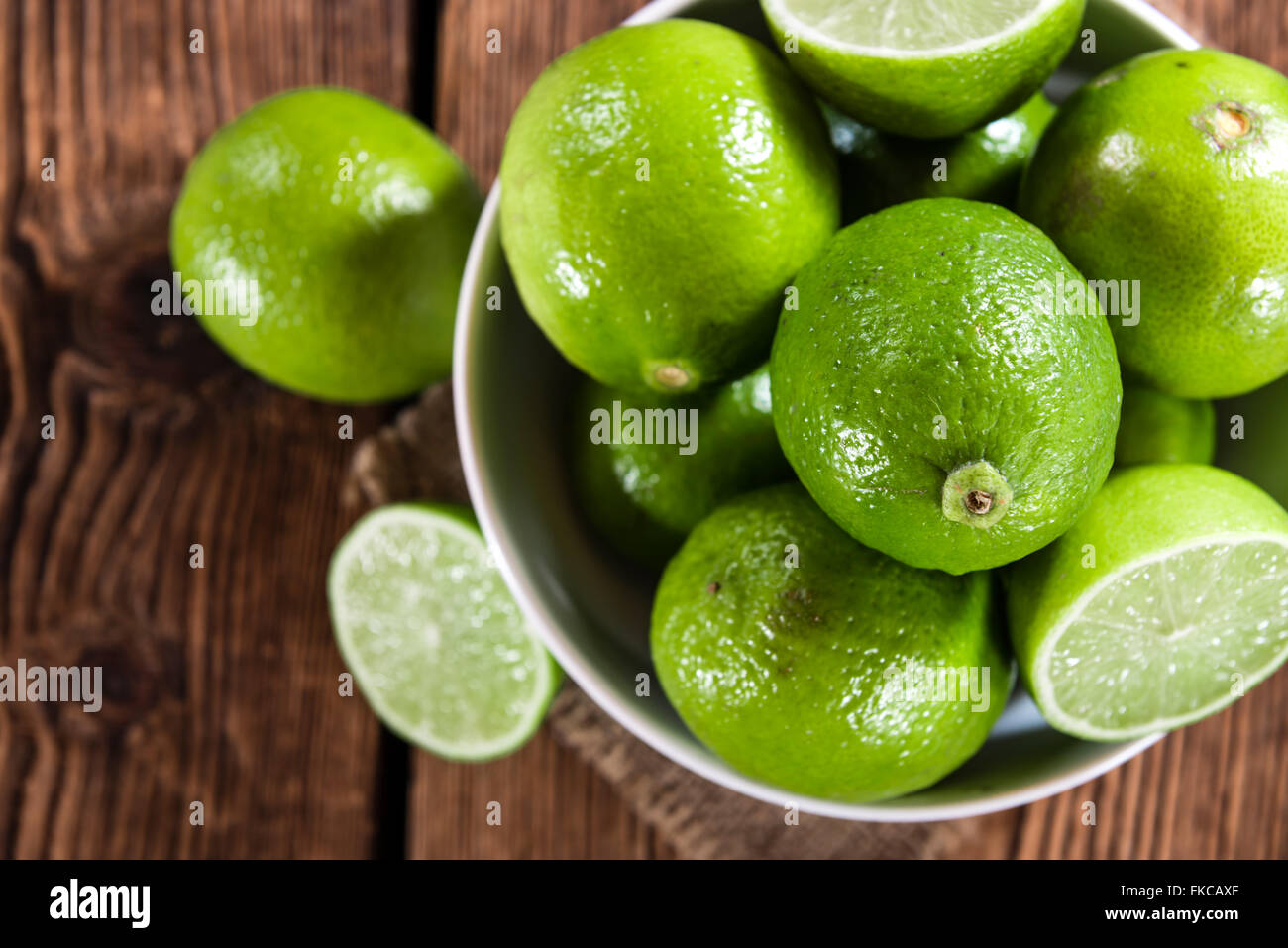 Limes on vintage wooden background (close-up shot) - Stock Image