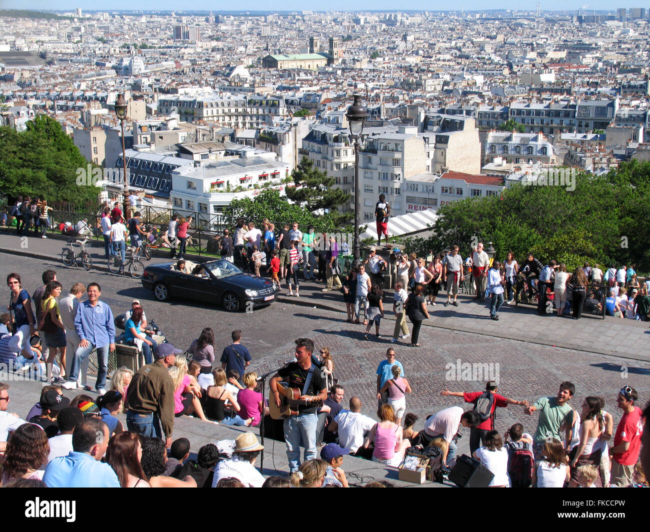 Tourists and buskers in Montmartre overlooking the panorama of Paris. - Stock Image