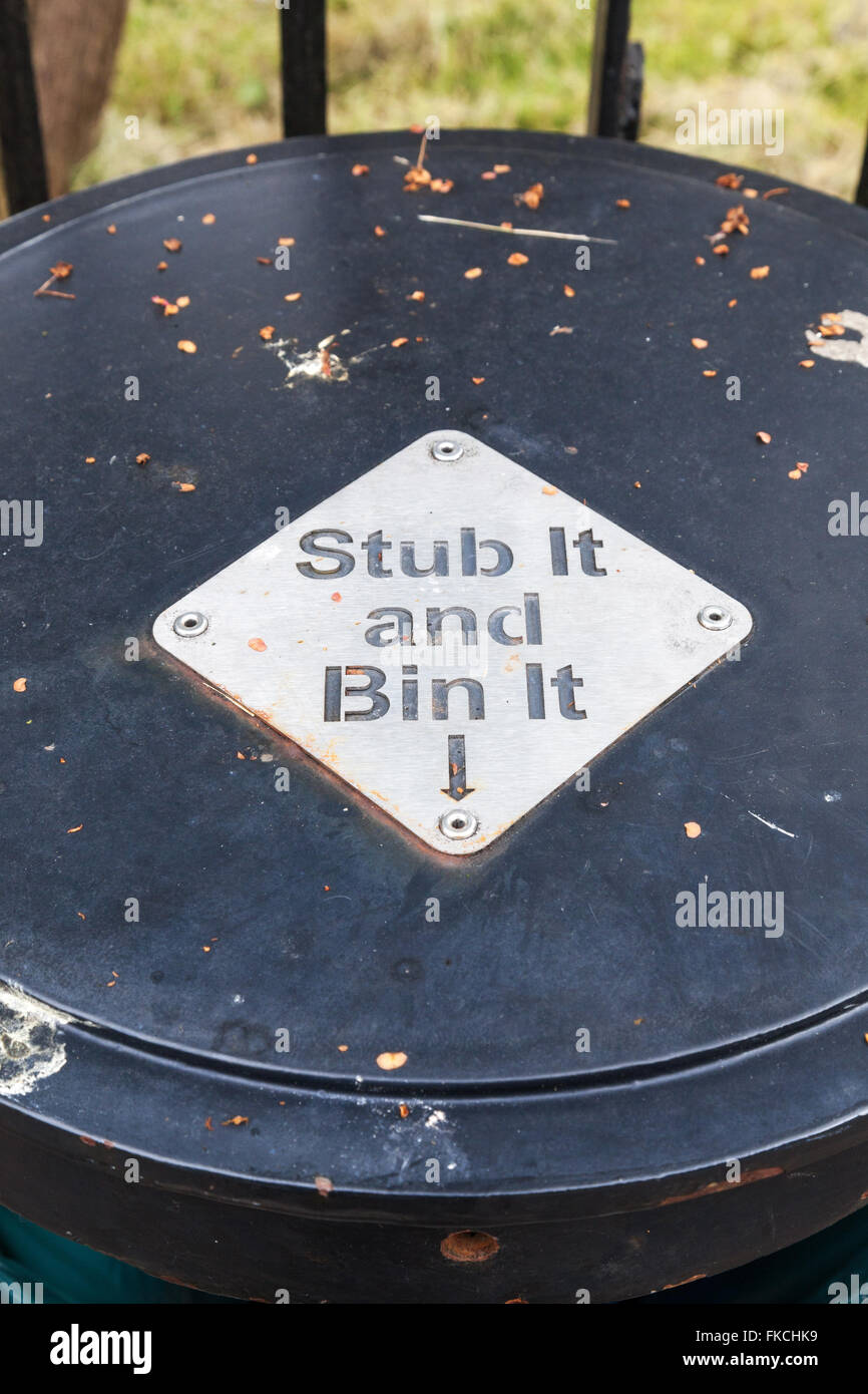 A waste bin with the words stub it and bin it on the top and a metal plate for stubbing out cigarettes - Stock Image
