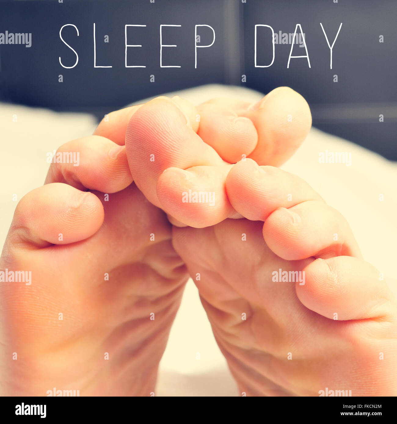 closeup of a young man rubbing his bare feet together in bed and the text sleep day - Stock Image