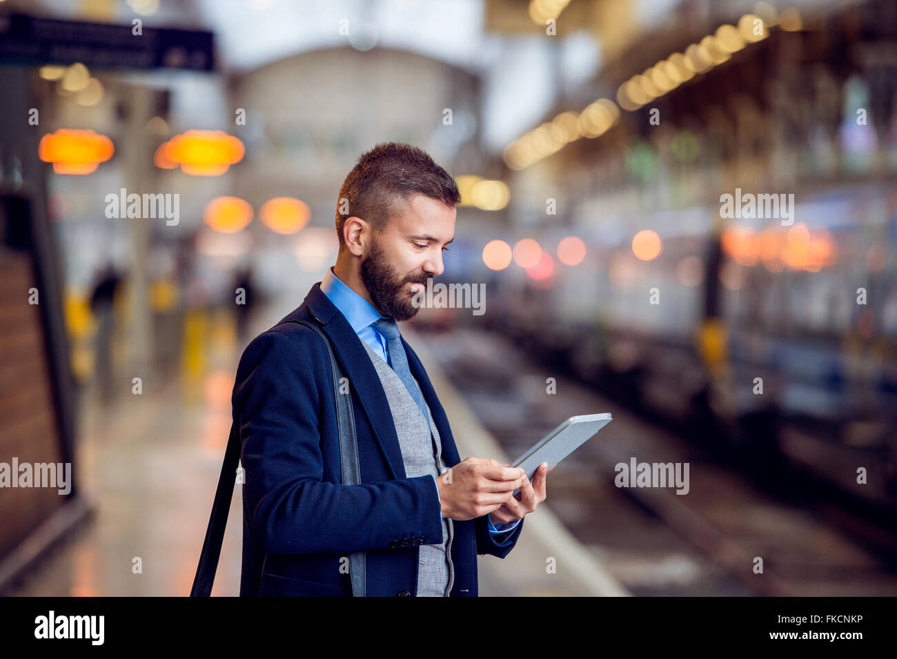 Hipster businessman with tablet, waiting, train platform - Stock Image