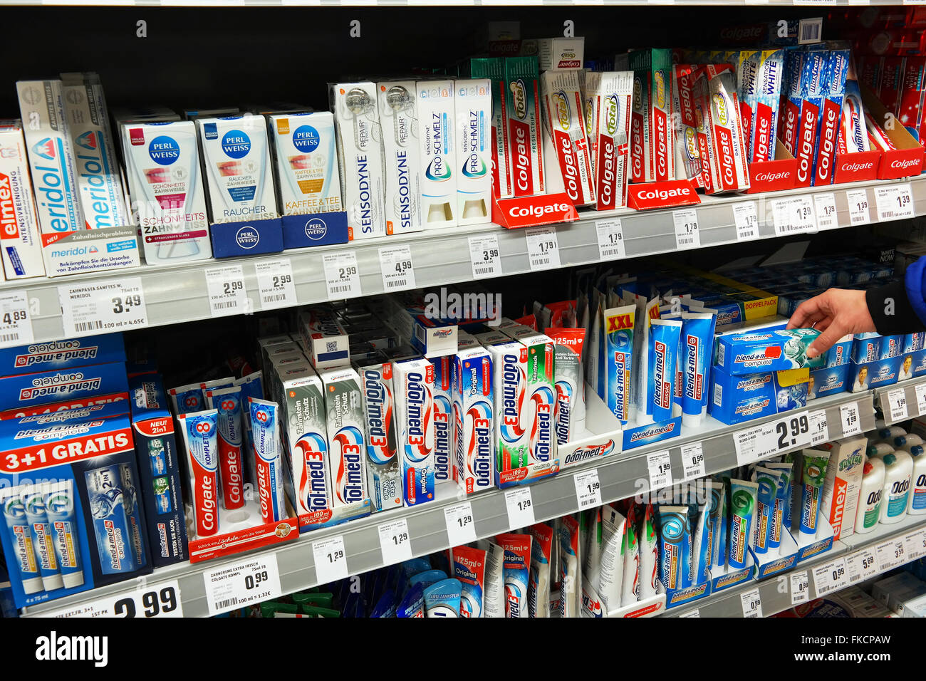 Selecting Toothpaste in a Supermarket - Stock Image